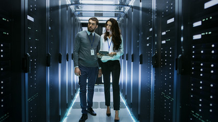 IT Specialist Showing Working Data Center with Rows of Rack Servers to His Female Colleague.