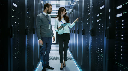 Female and Male IT Engineers Discussing Technical Details in a Working Data Center/ Server Room.