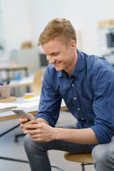 junger geschäftsmann schaut auf sein mobiltelefon