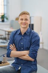 lächelnder junger mann sitzt mit verschränkten armen im büro