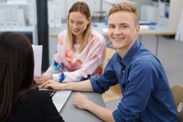 lächelnder mann arbeitet im team im büro