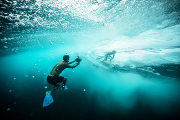 photographer underwater taking picture of surfer