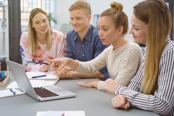 junges team sitzt zusammen und schaut gemeinsam auf laptop