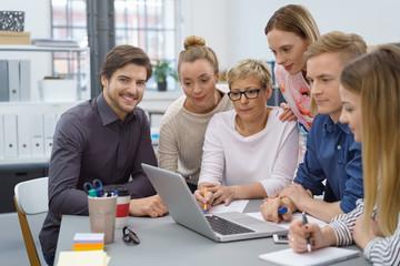 team im büro schaut gemeinsam auf informationen am laptop