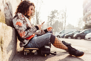 young woman using smart phone sitting skate