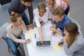 motiviertes team schaut gemeinsam auf notebook und plant etwas