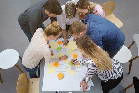 teilnehmer in einem workshop machen notizen auf bunten zetteln