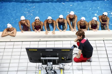 Masayo Imura, the coach of Japan's synchronised swimming team, reviews a training video with her swimmers at a pool in Tokyo