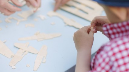 Granddad and his grandson are making wooden plane in the backyard on summertime