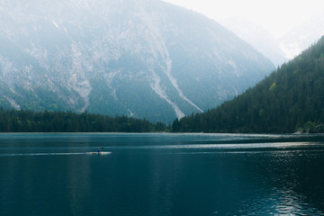 Person in Canoe boat paddling in a mountain lake
