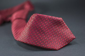 Beautiful red necktie isolated on black background.