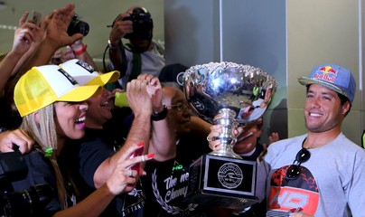De Souza of Brazil holds the World Surfing League World Title trophy as he arrives in Sao Paulo