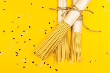Raw pasta on a yellow background in a rustic package.