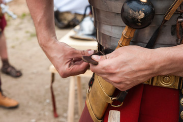 Roman soldier fastens war belt