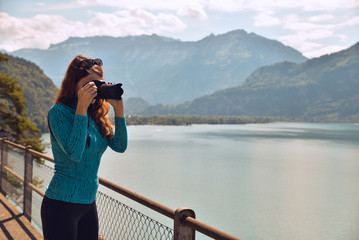 Tourist young girl holding camera and taking photos with beautiful landscape scenery in the back.