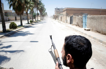A Kurdish fighter from the People's Protection Units (YPG) drives in pick up vehicle in Raqqa