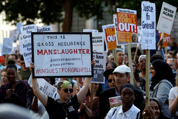 Demonstrators hold up banners during a march in Westminster, following the fire that destroyed The Grenfell Tower block, in north Kensington, West London