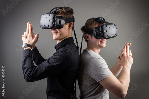 Shot of two young man standing with VR goggles and keep joysticks or