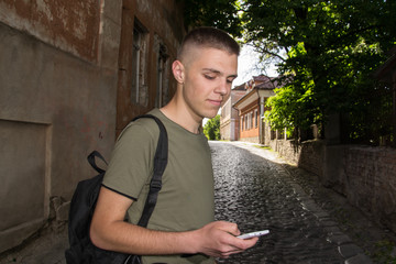 Half length portrait of male with retro style using cell telephone while standing in urban setting, man dressed in stylish clothes chatting on smart phone during walking in cool spring day, teenager