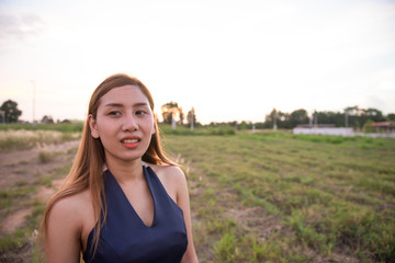 Beautiful asian woman think something  in the fields on sunset