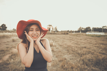Beautiful asian woman wear red hat in the fields vintage style,film tone,pastel