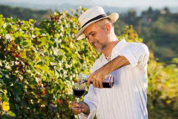Middle age worker tasting a vine