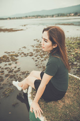 Beautiful thai woman very sad from unrequited love,rethink,think over,vintage style,dark tone,broken heart,asian girl,Sitting on a pier beside the dam