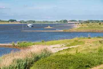 Ship sailing upstream along groynes on Waal river, Netherlands