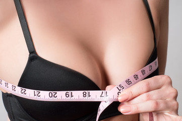 Young woman measures her breast with a measuring tape