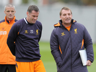 Liverpool's Jamie Carragher speaks with manager Brendan Rodgers (R) during training