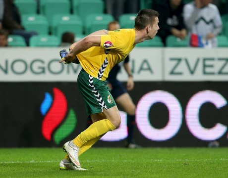 Lithuania's Linas Klimavicius tries to hide an opponent's boot during their Euro 2016 qualifying soccer match against Slovenia in Petrol arena in Ljubljana