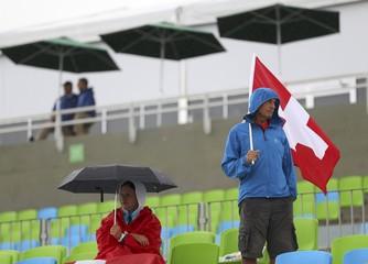 Spectators during the rain under umbrellas watch the rowing competion at Lagoa Stadium in Rio de Janeiro