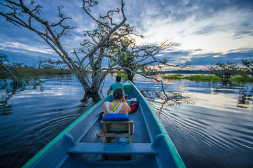 People enjoying the sunset from the river in Cuyabeno National Park, Ecuador