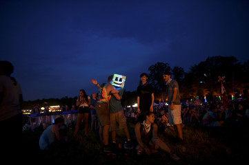 Kevin Wolymetz, 15, wears a smiley face mask and hugs a fellow festival goer during the Firefly Music Festival in Dover, Delaware, U.S.