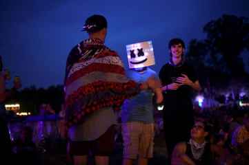 evin Wolymetz, 15, wears a smiley face mask during the Firefly Music Festival in Dover, Delaware, U.S.