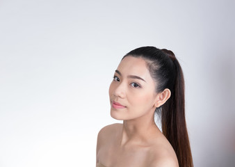 Portrait of a smiling young woman with natural make-up. beautiful asian girl standing against white background. Skincare, healthcare, studio shot.
