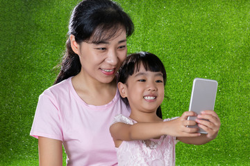 Asian Chinese mother and daughter playing with smartphone