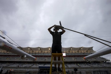 Rain clouds approach as a Red Bull Formula One pit crew member installs a camera ahead of the first practice session of the U.S. F1 Grand Prix at the Circuit of The Americas in Austin