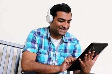 Happy handsome man typing on tablet while listening to music on head phones