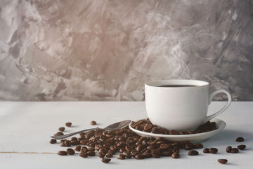 cup of coffee and coffee bean on white wooden background with loft wall style with light in concept relax time