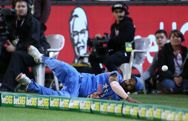 India's Dhawan fails to stop a six from the batting of Australia's Finch during their T20 cricket match at the Melbourne Cricket Ground