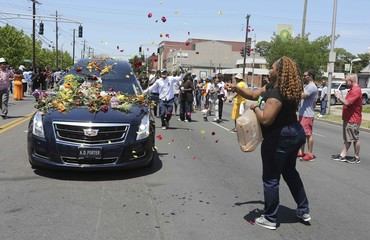 A woman showers the hearse carrying the body of Muhammad Ali with flowers as it drives down Broadway toward Cave Hill Cemetery in Louisville