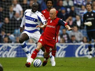QPR's Patrick Agyemang in action against Preston's Richard Chaplow (R)
