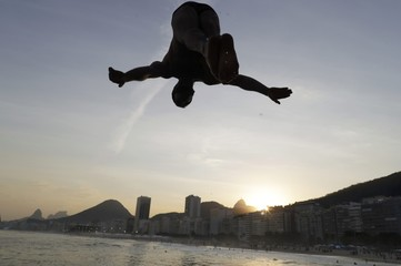 A bather dives into the ocean along Leme Beach in Rio de Janeiro