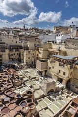 Traditional tannery with colorful basins in medina of Fes with town in background