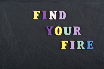 FIND YOUR FIRE word on black board background composed from colorful abc alphabet block wooden letters, copy space for ad text. Learning english concept.