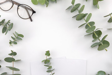 Two blank white cards decorated with baby eucalyptus leaves and glasses on white background with copy space