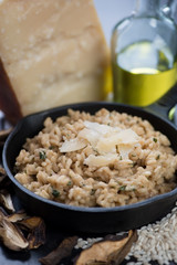 Risotto with ceps and parmesan cheese in a frying pan, close-up, vertical shot