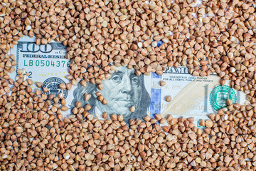 Grains of raw buckwheat and American money on the table