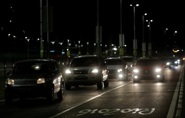 Cars drive in front of 2016 Rio Olympic Park in Rio de Janeiro